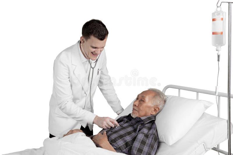Doctor que examina al paciente mayor fotografía de archivo libre de regalías