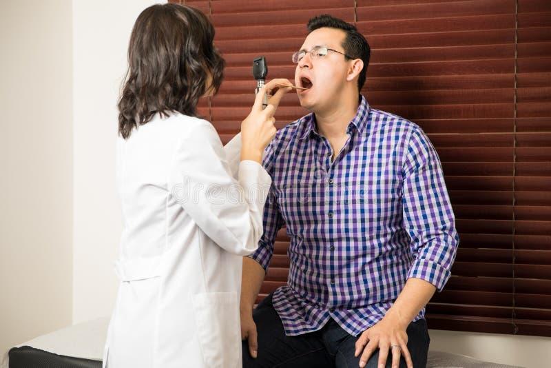 Doctor que examina la garganta paciente del ` s imágenes de archivo libres de regalías