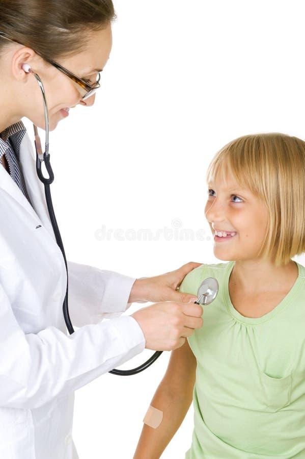 Doctor que examina a la muchacha del pequeño niño fotografía de archivo