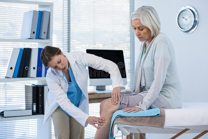 Doctor que examina la rodilla paciente imagen de archivo