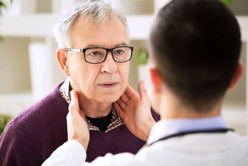 Doctor que examina las glándulas de linfa pacientes viejas imagenes de archivo