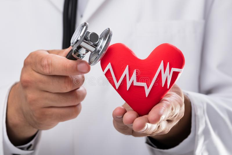 Doctor que examina ritmo cardíaco rojo con el estetoscopio foto de archivo