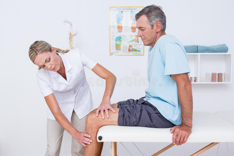 Doctor que examina su rodilla paciente foto de archivo