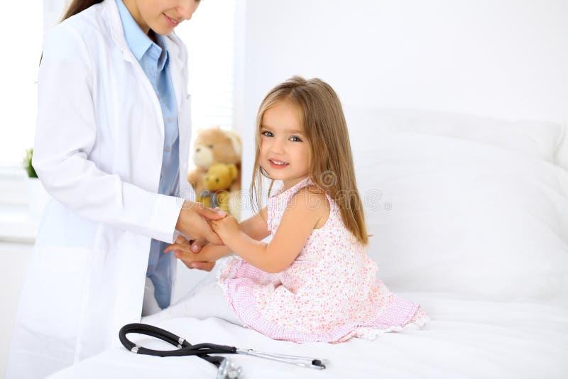 Doctor que examina a una niña por el estetoscopio fotos de archivo