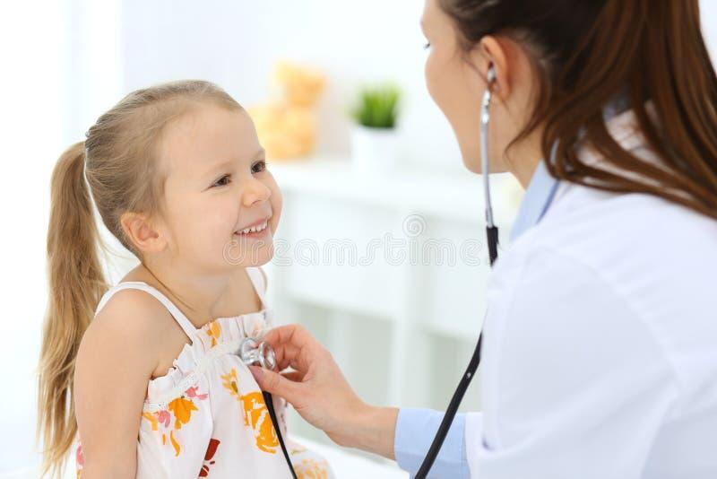 Doctor que examina a una niña por el estetoscopio Paciente sonriente feliz del niño en la inspección médica usual Medicina y imagenes de archivo