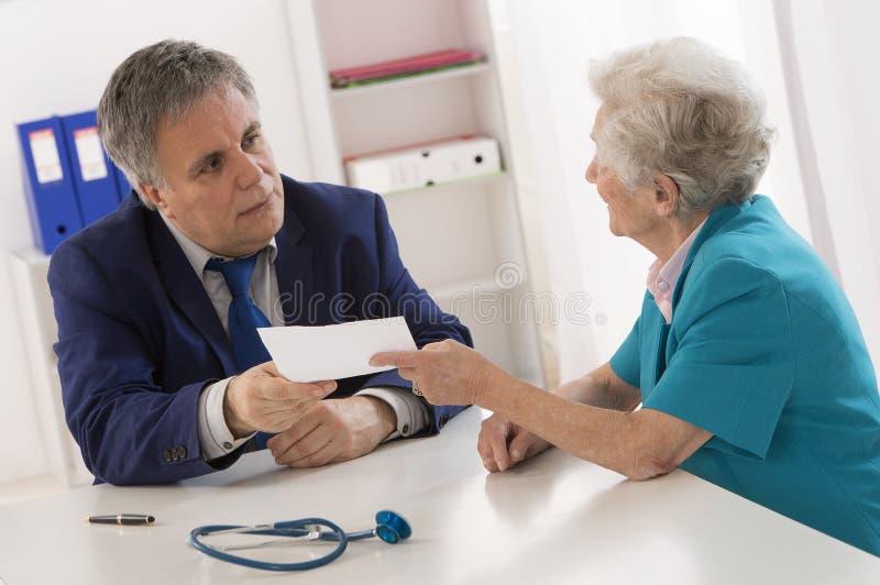 Doctor que explica diagnosis a su paciente mayor foto de archivo