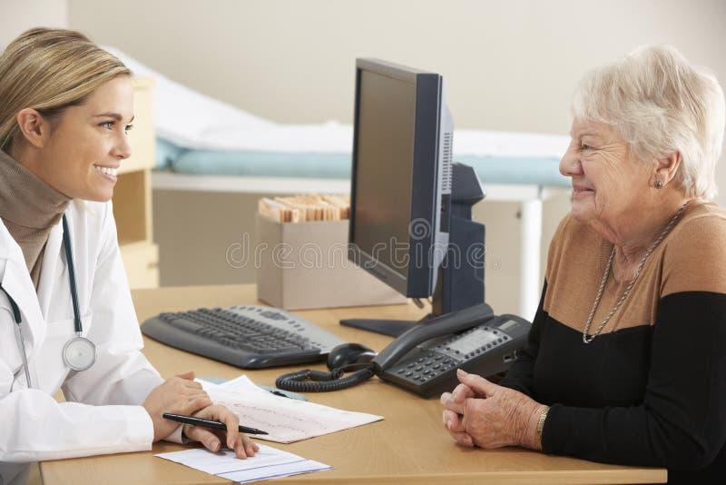 Doctor que habla con el paciente mayor de la mujer fotos de archivo