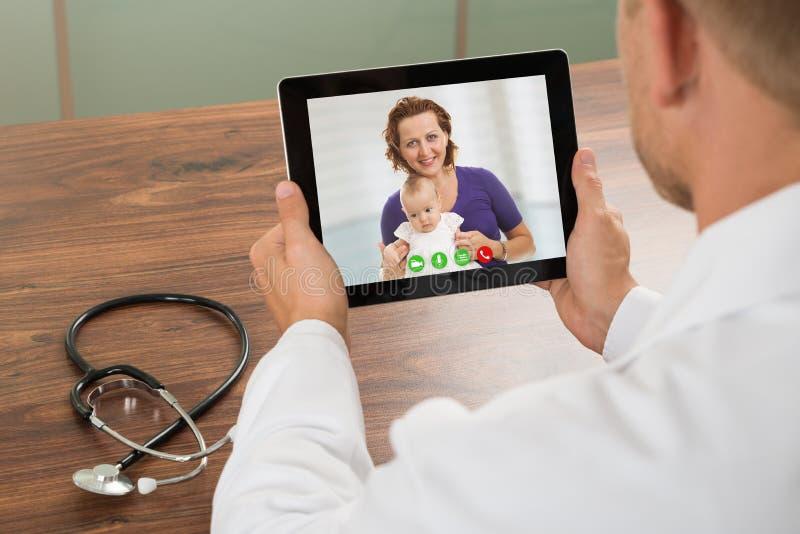 Doctor que habla con el paciente sobre la charla video del ordenador portátil foto de archivo