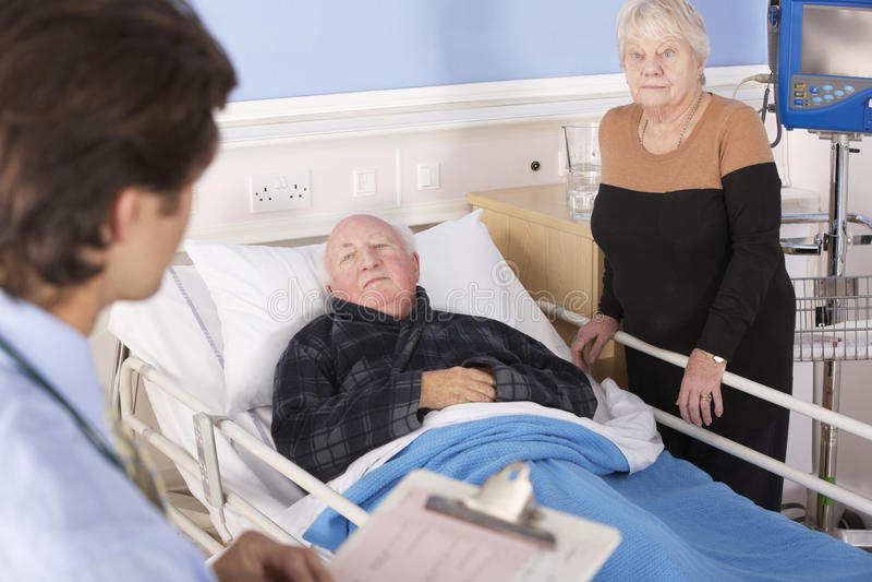Doctor que habla con los pares mayores en hospital foto de archivo