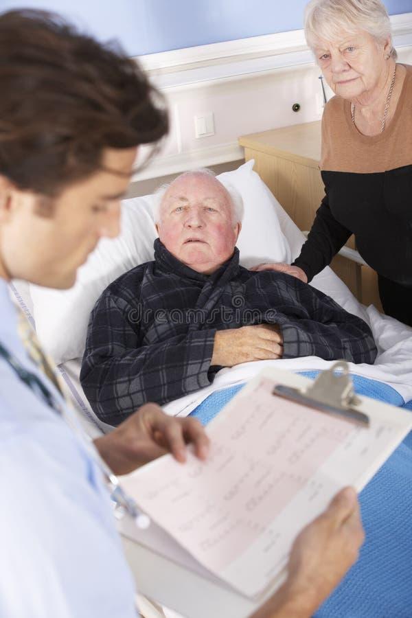 Doctor que habla con los pares mayores en hospital imagen de archivo
