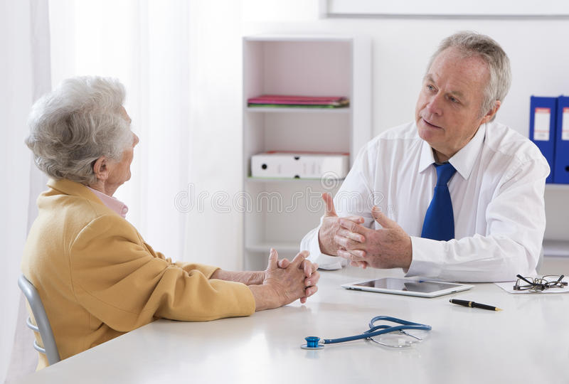 Doctor que habla con su paciente mayor femenino imagen de archivo