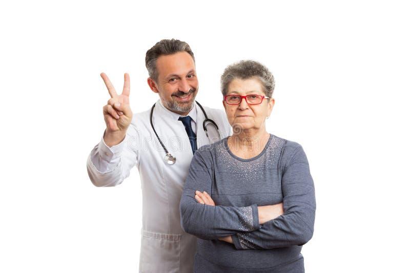 Doctor que hace la muestra de la paz o de la victoria con el paciente foto de archivo