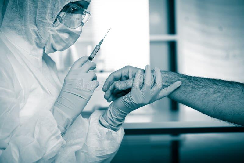 Doctor que inyecta la medicación en el brazo de los pacientes imagenes de archivo