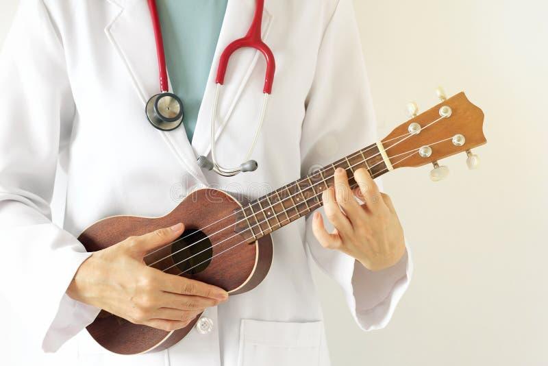 Doctor que juega el ukelele, concepto de la terapia de música foto de archivo