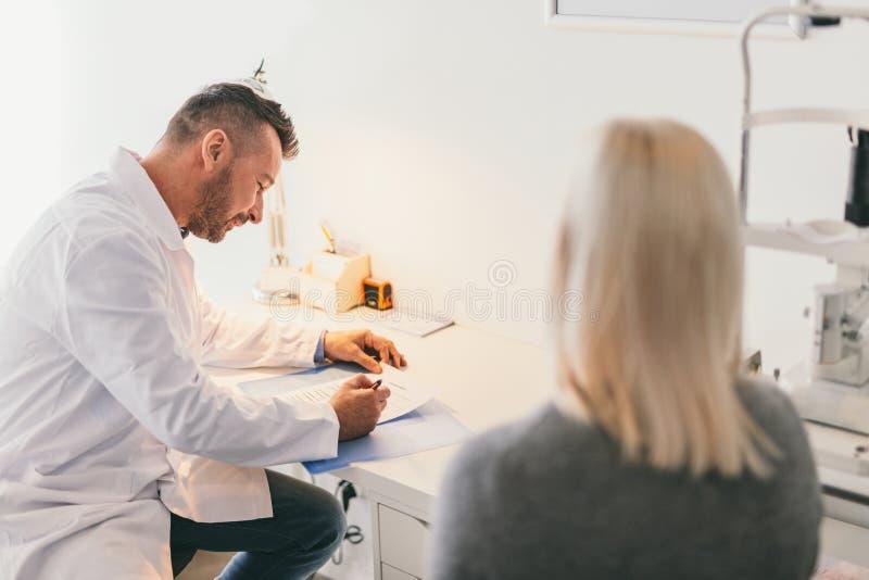 Doctor que llena el cuestionario médico de un paciente foto de archivo libre de regalías