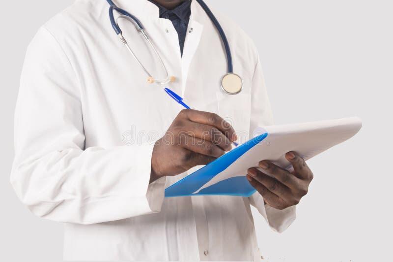 Doctor que llena el formulario médico foto de archivo