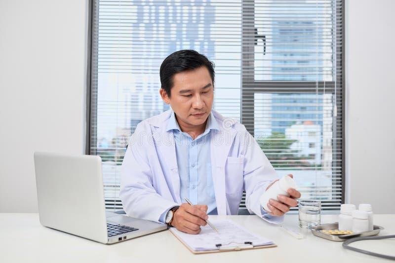 Doctor que llena encima de un formulario de la historia mientras que consulta al paciente fotos de archivo libres de regalías