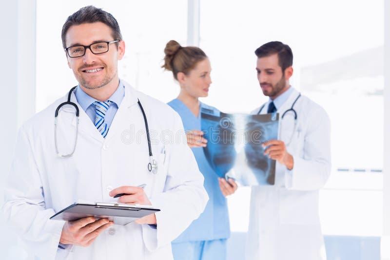 Doctor que lleva a cabo informes con los colegas que examinan la radiografía foto de archivo