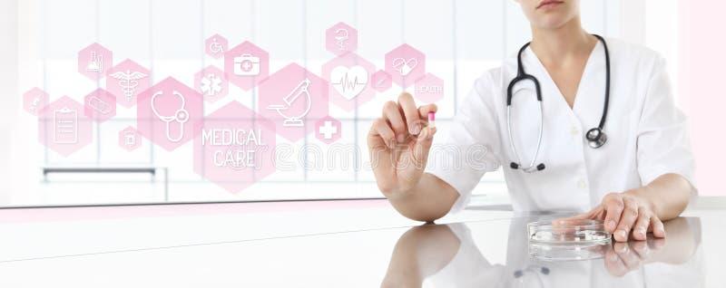 Doctor que lleva a cabo la medicina de la píldora con los iconos rosados Concepto del cuidado médico foto de archivo