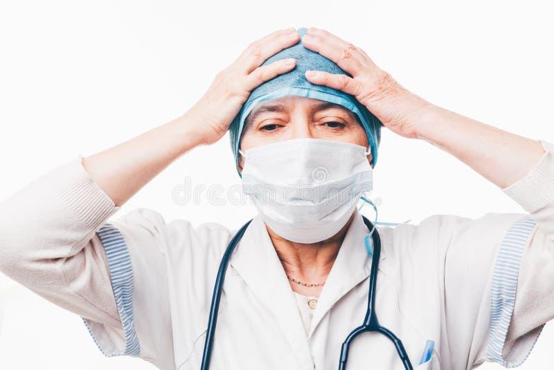Doctor que lleva a cabo las manos en la cabeza imagenes de archivo