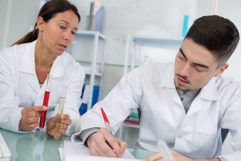 Doctor que lleva a cabo sangre roja en tubo de ensayo con el aprendiz imagen de archivo