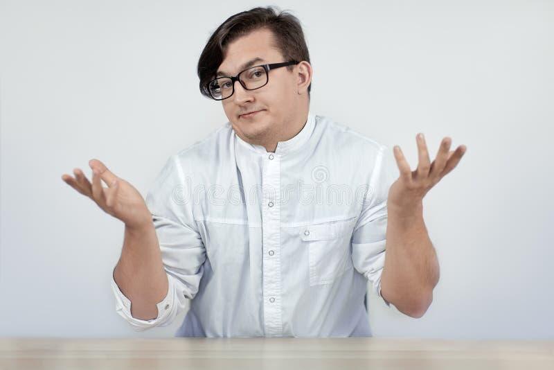 Doctor que lleva del hombre hermoso joven o capa blanca de los scientis con las manos del gesto de la incredulidad para arriba y  foto de archivo