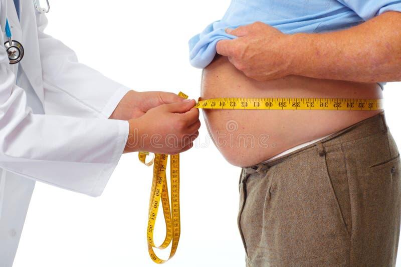 Doctor que mide el estómago obeso del hombre fotos de archivo libres de regalías