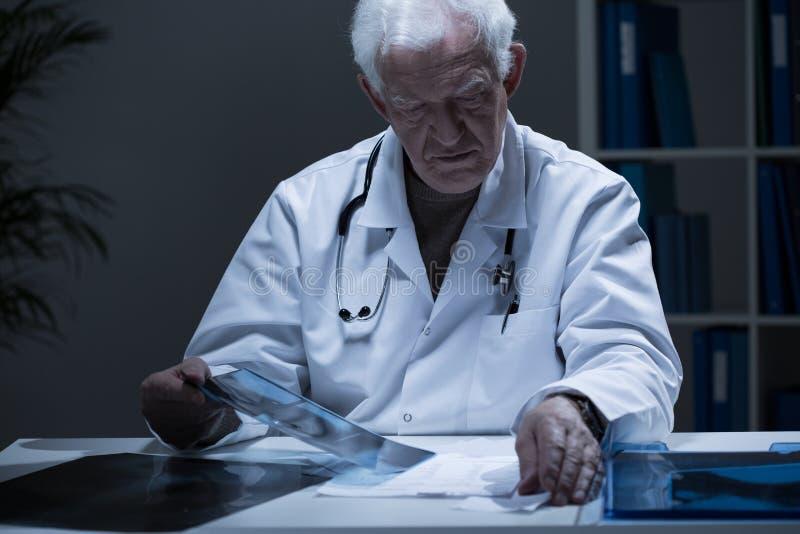 Doctor que mira imagen de la radiografía fotografía de archivo