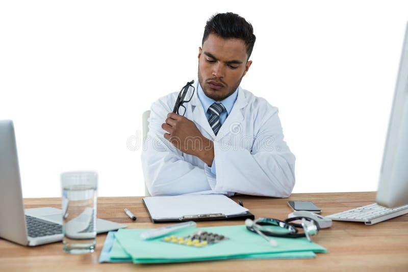 Doctor que mira informe médico el escritorio fotografía de archivo