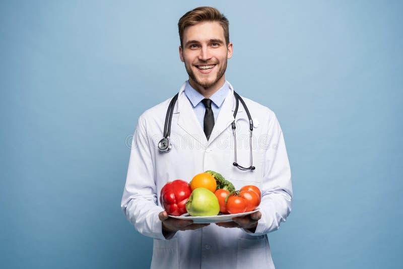 Doctor que mira la cámara y que sostiene la placa de las verduras frescas aisladas en concepto azul claro, sano de la consumición foto de archivo libre de regalías