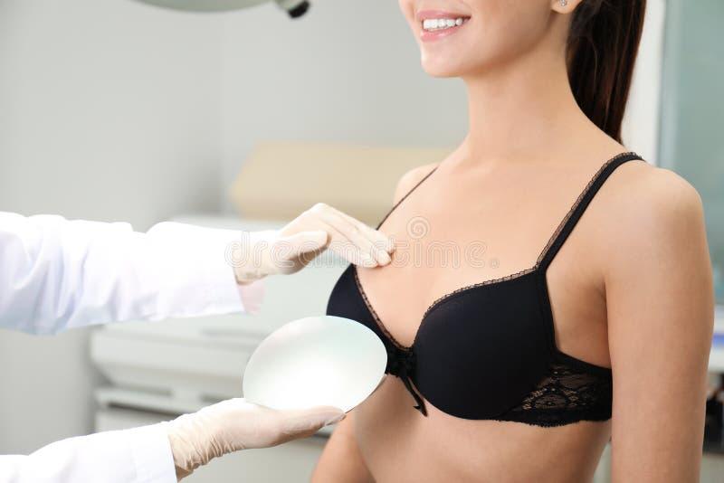 Doctor que muestra el implante del silicón para el aumento del pecho al paciente en la clínica, primer fotografía de archivo