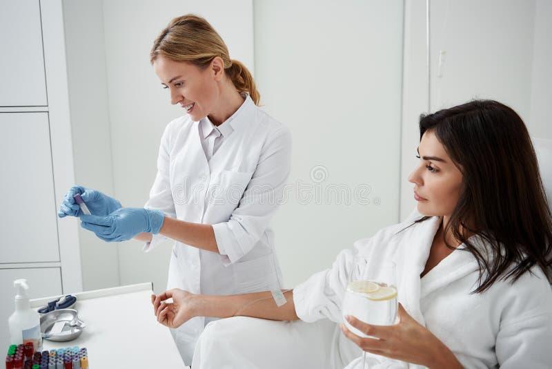 Doctor que prepara el líquido para IV la infusión mientras que señora joven que se sienta en butaca fotografía de archivo libre de regalías