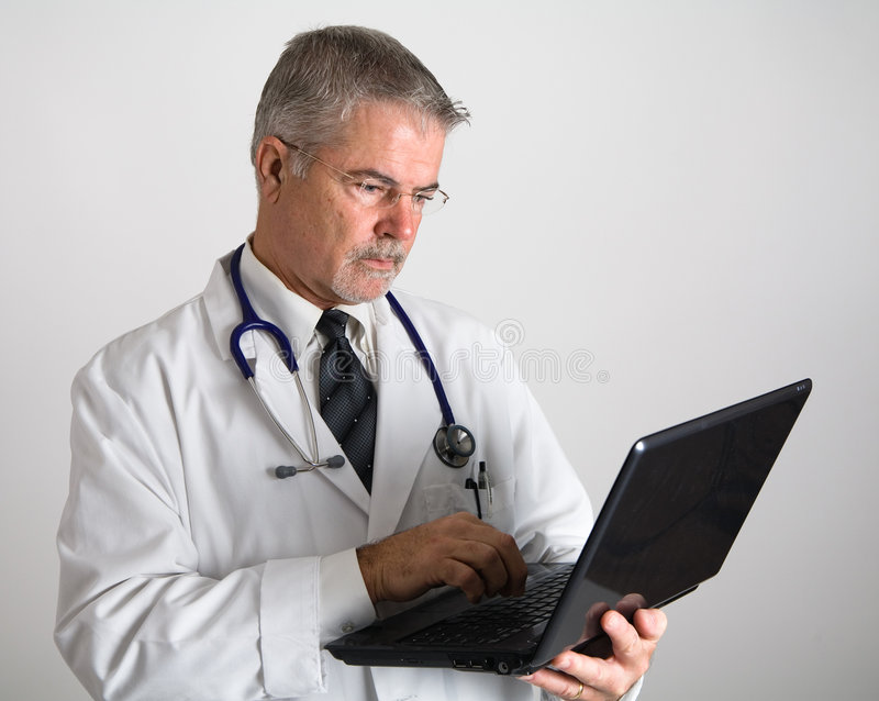 Doctor que pulsa en el ordenador foto de archivo