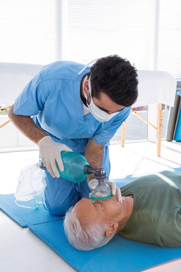 Doctor que realiza la resucitación en paciente fotos de archivo