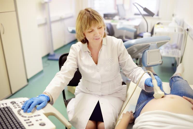 Doctor que realiza ultrasonido en mujer embarazada en clínica Maternidad del seguro m?dico M?dico de cabecera para la gestaci?n m fotografía de archivo