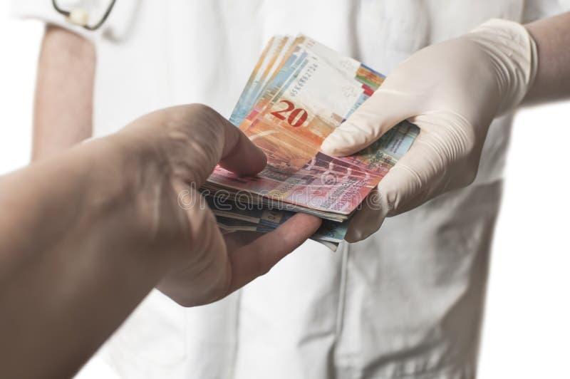 Doctor que recibe una gran cantidad de billetes de banco suizos como soborno imagenes de archivo