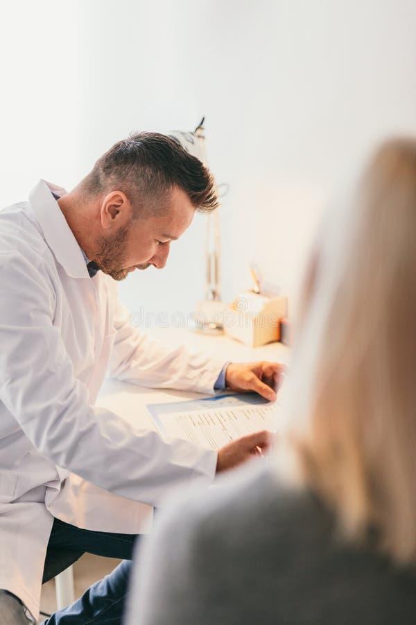 Doctor que rellena un impreso en blanco de un paciente imagenes de archivo