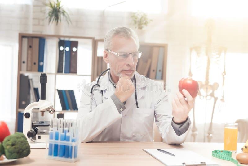 Doctor que se sienta en el escritorio en oficina El doctor está sosteniendo la manzana roja fresca imagenes de archivo