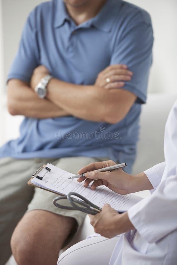Doctor que siente historial médico imagen de archivo libre de regalías