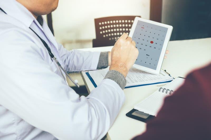 Doctor que sostiene la tableta y que señala en remin de la cita del calendario imagen de archivo
