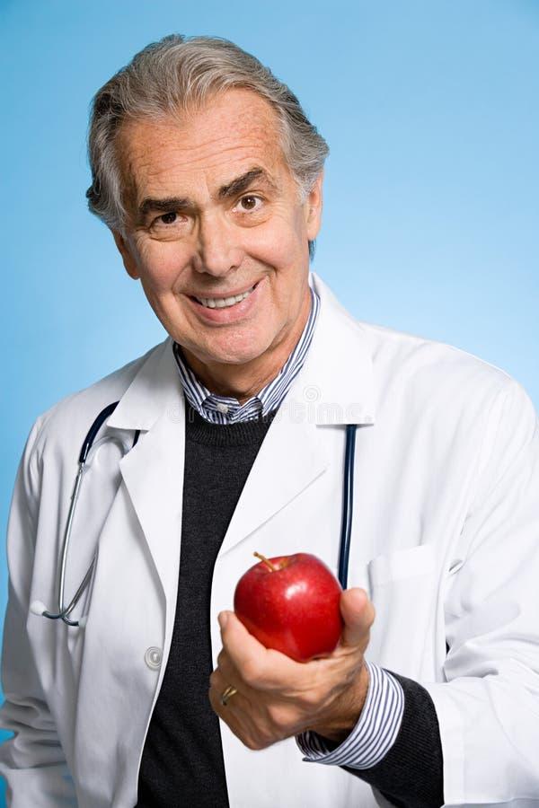 Doctor que sostiene una manzana foto de archivo