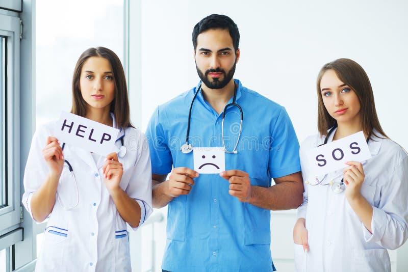 Doctor que sostiene una tarjeta con sonrisa del símbolo Ayuda y SOS, c médica foto de archivo