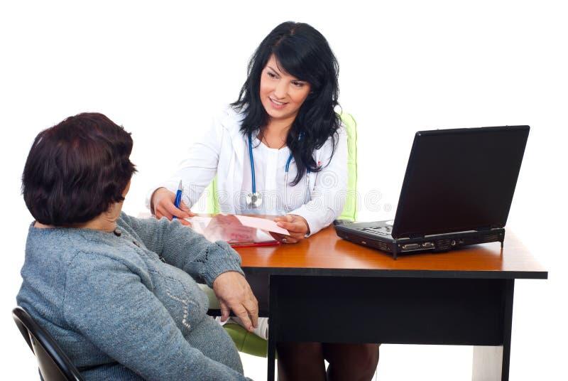 Doctor que tiene conversación con el paciente en oficina fotografía de archivo libre de regalías