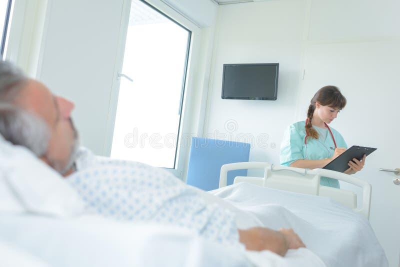 Doctor que toma notas del paciente del hombre que miente en cama de hospital fotografía de archivo libre de regalías