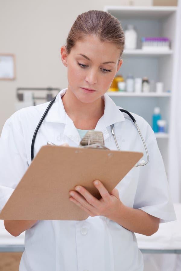 Doctor que toma notas sobre el sujetapapeles imagenes de archivo