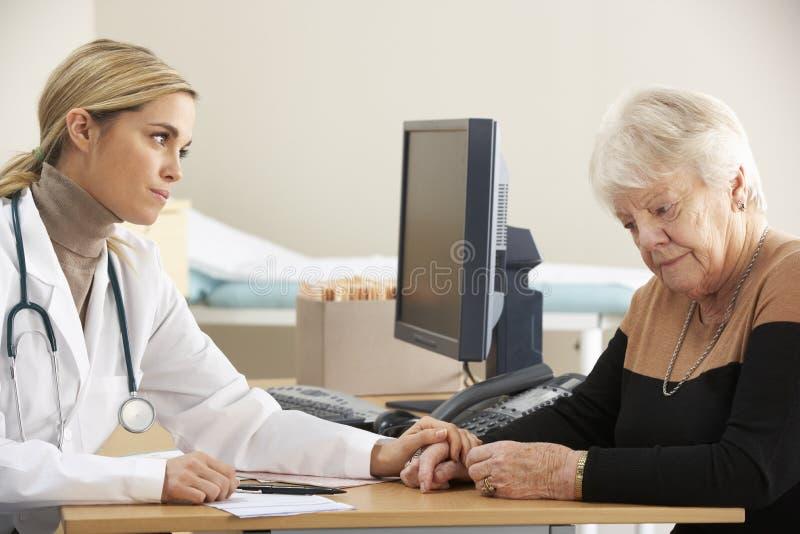 Doctor que tranquiliza al paciente mayor de la mujer foto de archivo libre de regalías