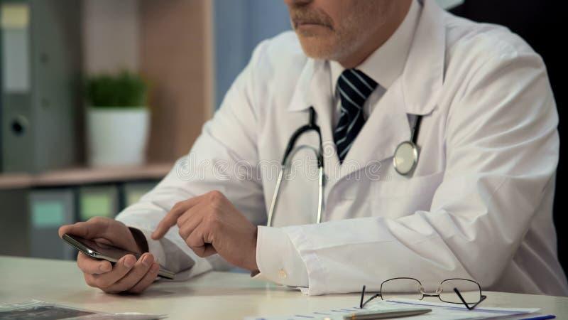 Doctor que usa el nuevo uso médico en el artilugio, buscando la información necesaria foto de archivo