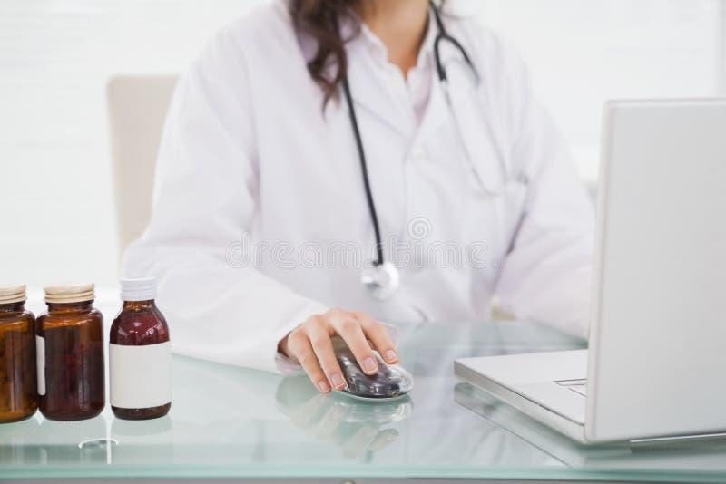Doctor que usa el ordenador portátil cerca de las botellas de píldora fotos de archivo