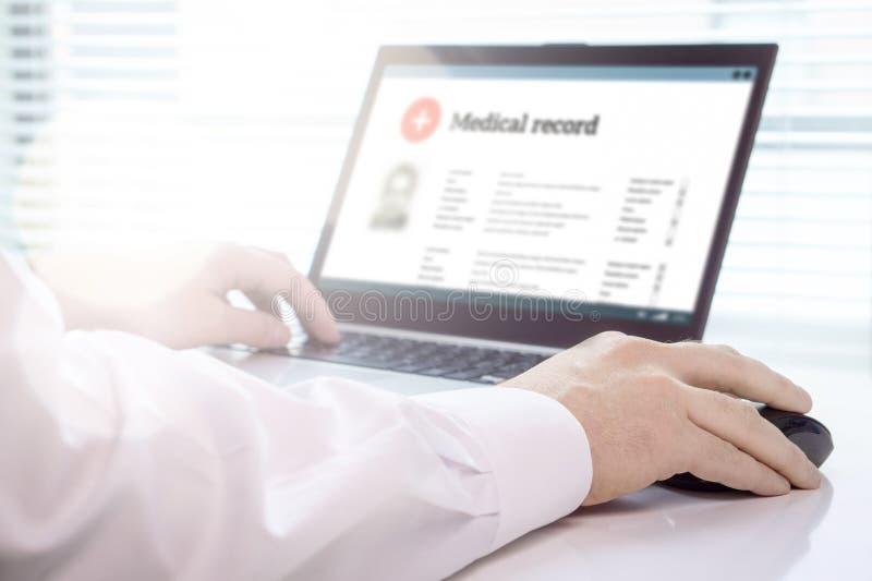 Doctor que usa el ordenador portátil y el sistema electrónico del informe médico EMR fotografía de archivo