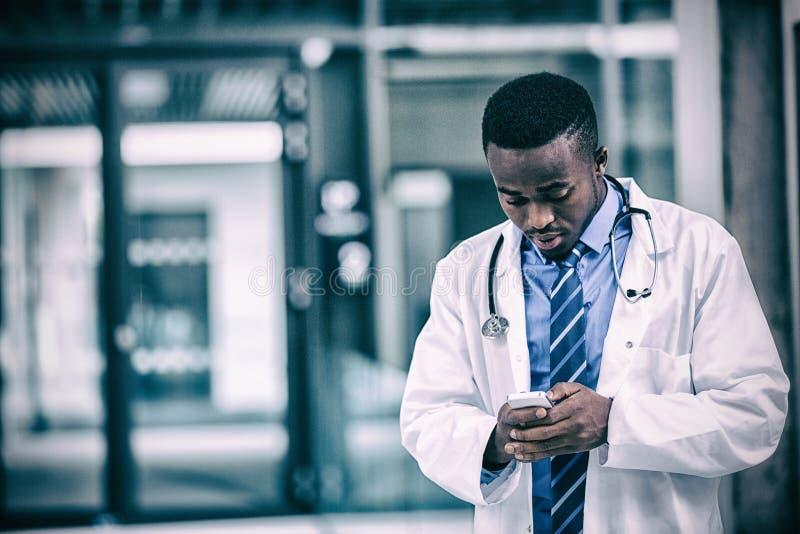 Doctor que usa el teléfono móvil fotos de archivo libres de regalías
